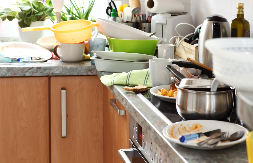 Messy and cluttered kitchen with pots and pans and dirty dishes stacked on the granite countertop and range. Clutter can be a serious safety issue, particularly for older adults.