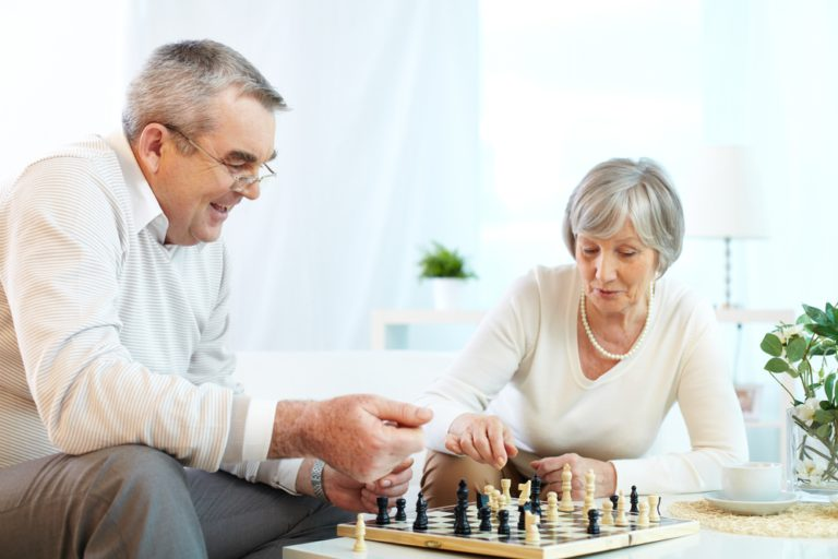 A senior man and woman playing a game of chess. Board games are one strategy to help keep the mind active and agile.