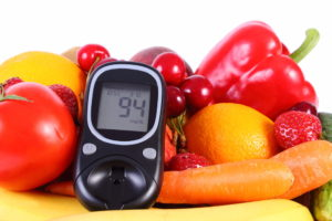 Fruit and vegetables and a glucose monitor. Lifestyle and diet modifications can make living with diabetes more manageable.
